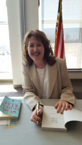 Laura McBride seated and ready to sign copies of her debut novel. (Photo by the author.)