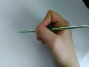 Holding the crochet needle like a pencil. Photo by the author.